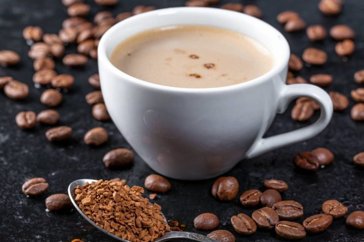 a cup of coffee on a table with sprinkled coffee beans